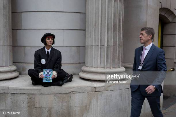 A City businessman walks through Bank as environmental activists protest about Climate Change during the blockade outside the Bank of England in the...