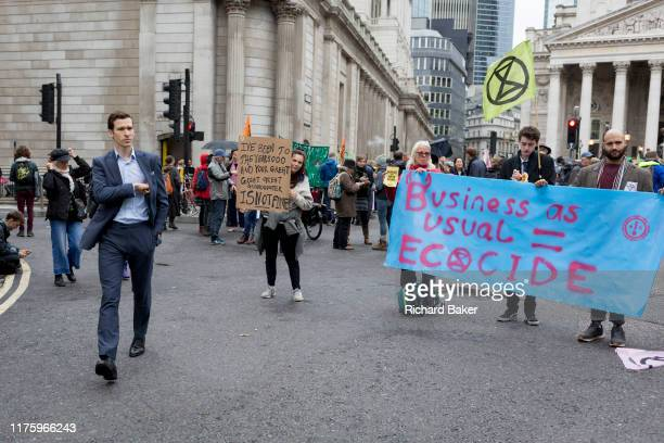 City businessmen and financiers walk through Bank as environmental activists protest about Climate Change during the blockade outside the Bank of...
