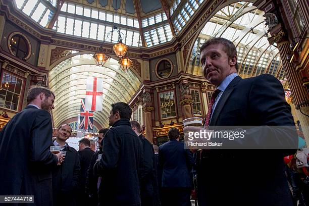 City businessmen drink in Leadenhall Market in the City of London on England's national St George's Day the 23rd April