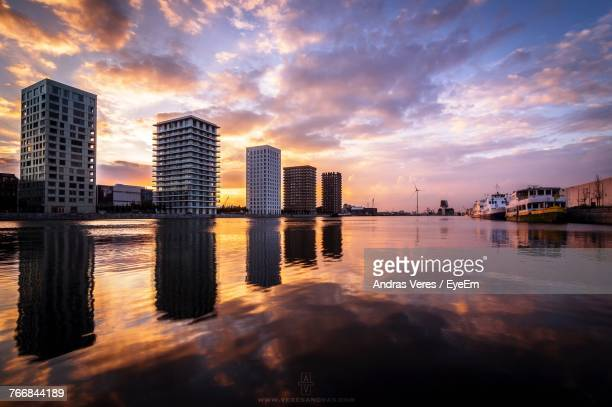 city by river against sky during sunset - antwerpen stad stockfoto's en -beelden