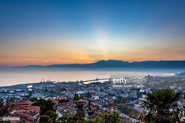 city by river against sky during sunset - rijeka stock pictures, royalty-free photos & images