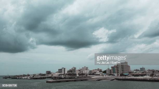city by sea against storm clouds - zhanjiang stock photos and pictures