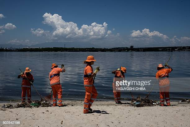 City cleaners collect floated debris on a beach at Guanabara bay in Rio de Janeiro Brazil on December 26 2015 The bay where the nautical sports of...