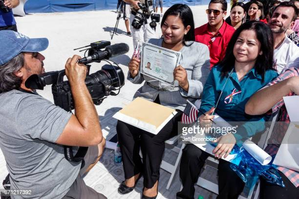A city commissioner congratulates a woman with a Certificate of Naturalization at the Oath of Citizenship Ceremony