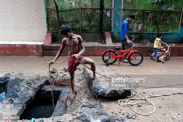 JATRABARI DHAKA BANGLADESH City Corporation young sewer cleaner cleans road manholes near Jatrabari Dhaka For this oneday work sewer cleaner get...