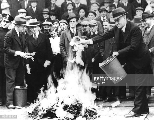 City council man Mr Barlow and Treasury Secretary Mr Jil Martin burning 100000 dollars of scrip money April 1933 United States National archives...