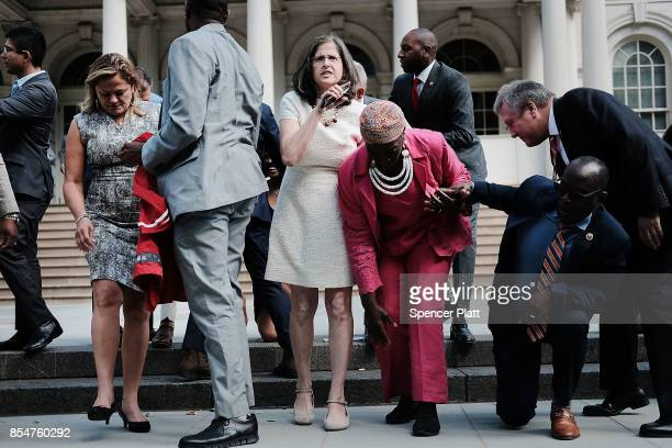 City Council Members get up after 'taking a knee' on the steps of City Hall in reaction to President Donald Trump's condemnation of NFL players who...