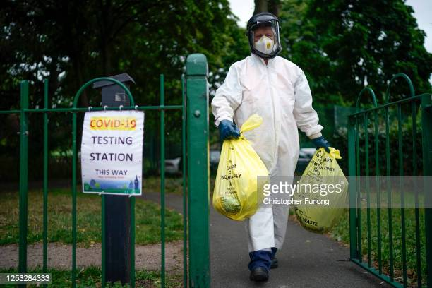 City council worker carries rubbish from a coronavirus testing centre at Spinney Park which will be incinerated on June 29, 2020 in Leicester,...