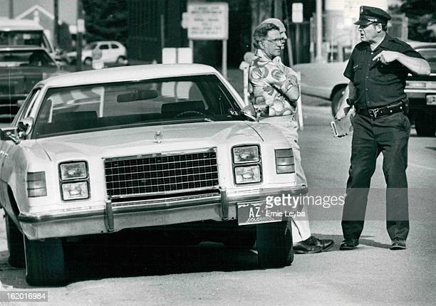 MAY 6 1979 MAY 7 1979 City Councilman Larry Perry Leans On Car As Policeman James 'Buster' Snider Talks With Him Perry who is struggling for...