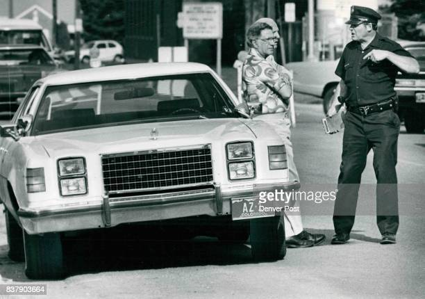 City Councilman Larry Perry Leans On Car As Policeman James 'Buster' Snider Talks With Him Perry who is struggling for reelection on May 15 has...