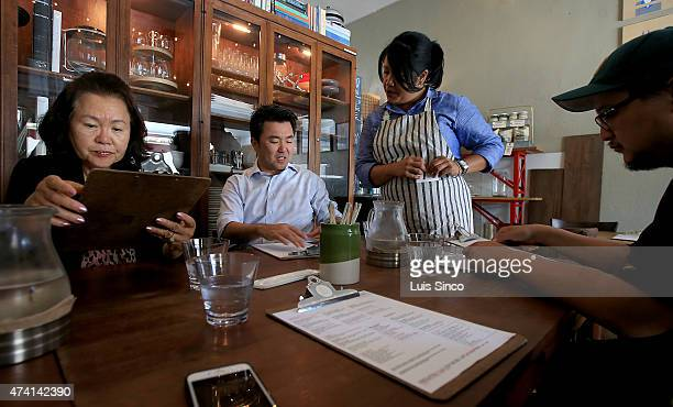 City Councilman-elect David Ryu celebrates his election victory with his mother Michelle Ryu, left, restaurant owner Jennyfer Rodgers, standing, and...