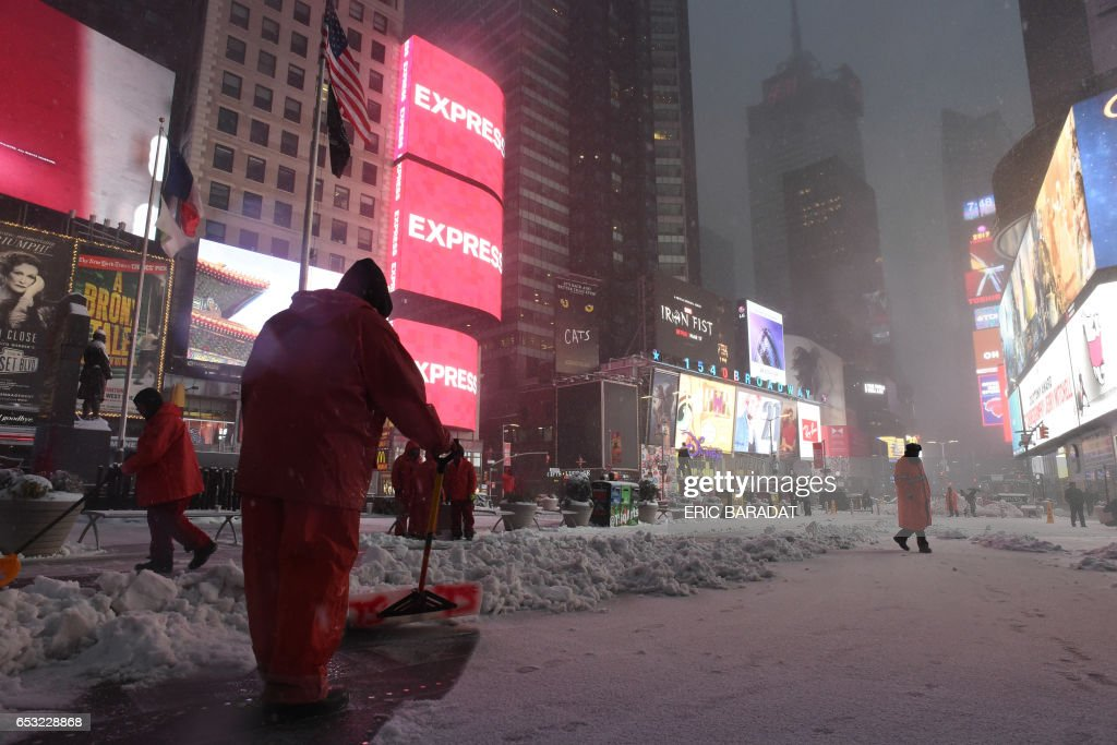 City employees clear the sidewalk in Times Square during a snowstorm in New York on March 14, 2017. Winter Storm Stella dumped snow and sleet Tuesday across the northeastern United States where thousands of flights were canceled and schools closed, but appeared less severe than initially forecast. After daybreak the National Weather Service (NWS) revised down its predicted snow accumulation for the city of New York, saying that the storm had moved across the coast. PHOTO / Eric BARADAT