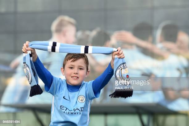 City fan seven year old Bobby English poses on his father's shoulders as Manchester City supporters gather outside the Etihad Stadium in Manchester...