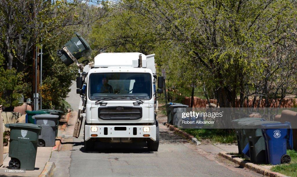 City garbage truck picks us refuse : News Photo