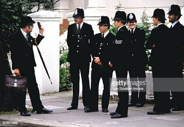 City gent preacher gets across his message to skeptical Metropolitan police officers on a London street.