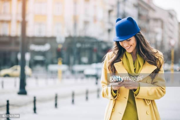 Mädchen aus der Stadt mit Smartphone und Katze-Hut