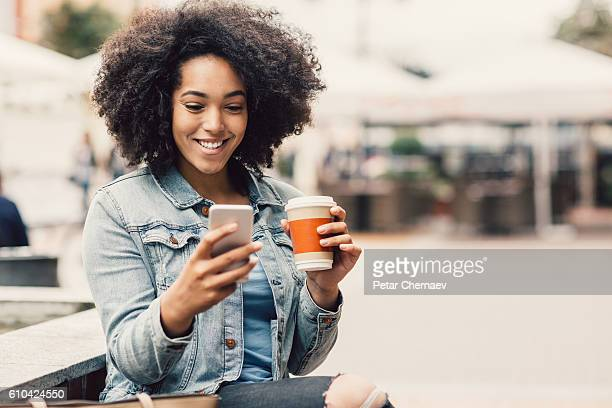 city girl with smart phone and coffee cup - creole ethnicity stock pictures, royalty-free photos & images