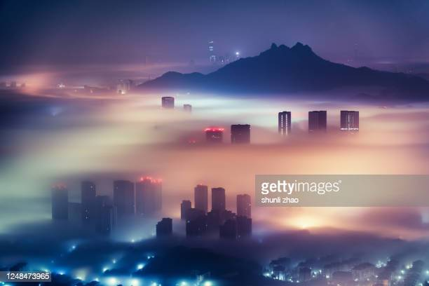 city in the mist at night - smog stock pictures, royalty-free photos & images