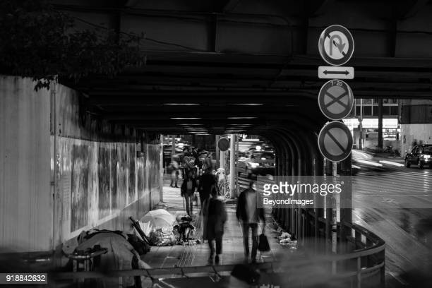 雨の中での都市: 絶望的なホームレス人々 は雨の夜に橋の下に避難