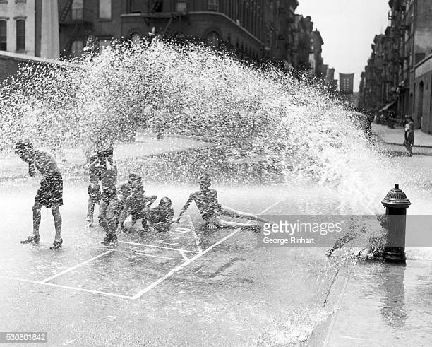 City kids beat the heat of summer with the aid of an open fire hydrant Undated photograph BPA2# 4343
