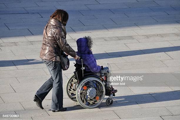 City Köln: Frau im Rollstuhl wird geschoben Köln