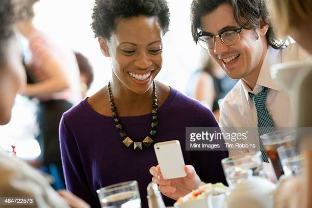 City life. A group of people sitting in a cafe or bar around a table. Men and women checking their smart phones.