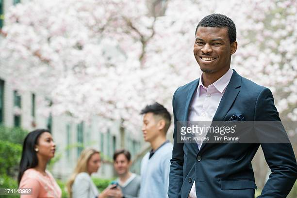 City life in spring. Young people outdoors in a city park. A man in a suit, smiling. Four people in the background. Using cell phones.