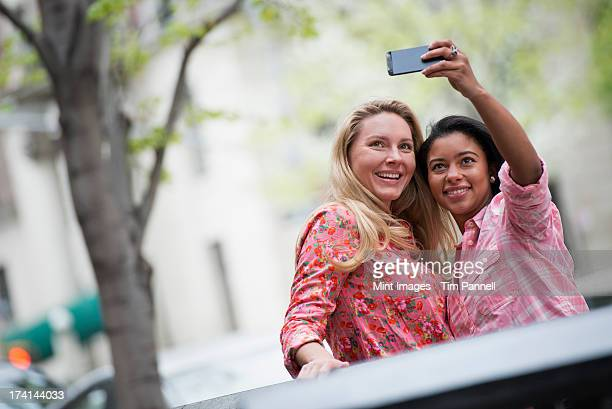 City life in spring. Young people outdoors in a city park. Two women taking a self portrait or selfy with a smart phone.