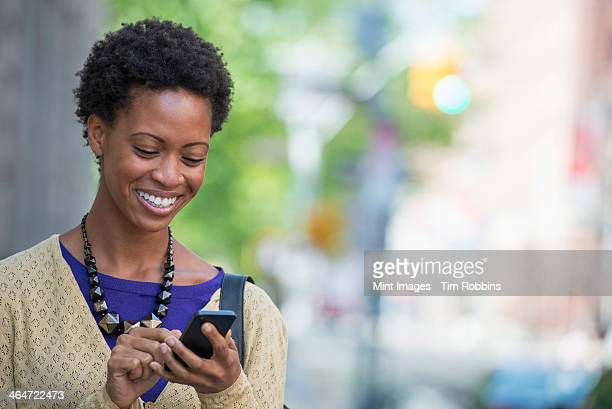 City life. People on the move. A woman in a purple dress checking her smart phone.