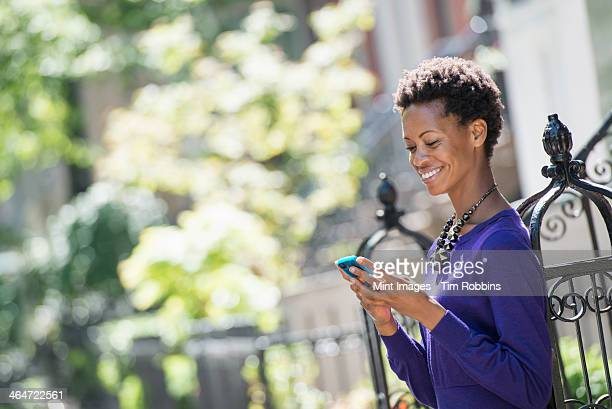 city life. people on the move. a woman in a purple dress checking her smart phone. - purple dress stock pictures, royalty-free photos & images