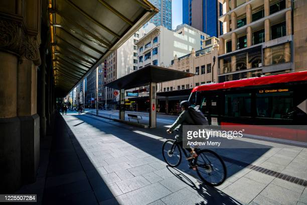 city life with cyclist and red tram, light rail station, australia - coronavirus australia stock pictures, royalty-free photos & images