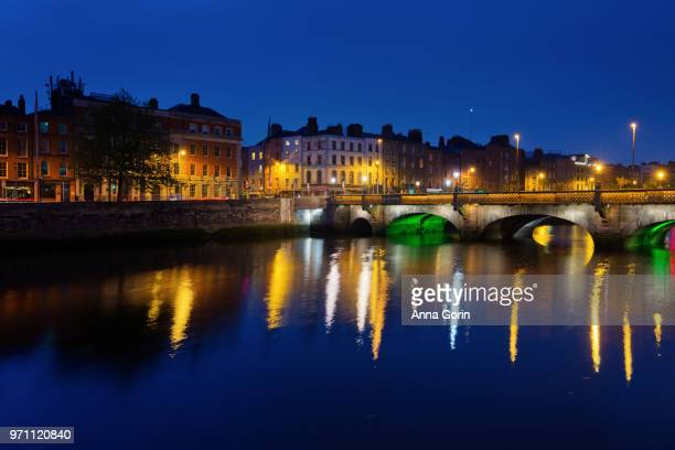 City lights of downtown Dublin, Ireland, reflected in River Liffey at dusk