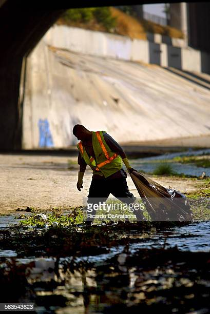 City maintenance worker picking up trash from the Los Angeles River. This was after City Attorney Rocky Delgadillo, other city officials and...