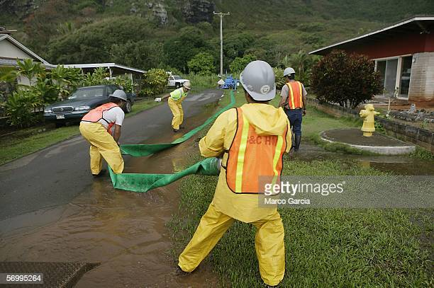 City maintenance workers drag a drainage hose away towards the beach to pump water out of a swollen creek on March 3, 2006 in the town of Ka'aa'wa on...