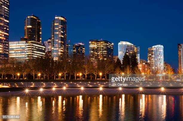 city of bellevue at twilight with city lights reflected in pond at downtown park. - bellevue skyline stock pictures, royalty-free photos & images