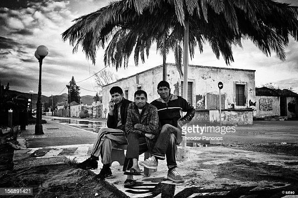 City of Kos Greece Three workers from Pakistan sit under a sun umbrella