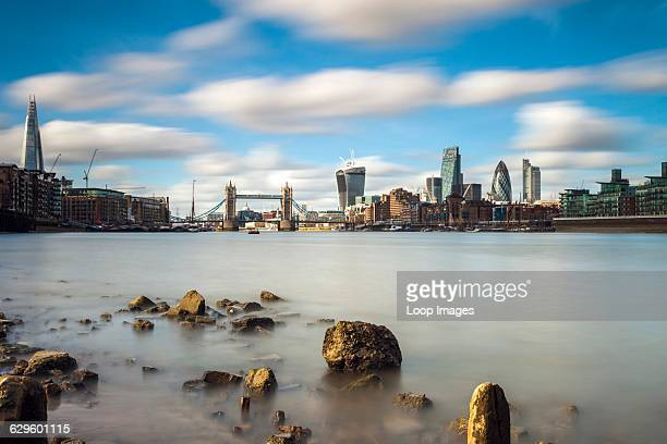 City of London across the Thames at low tide The City England