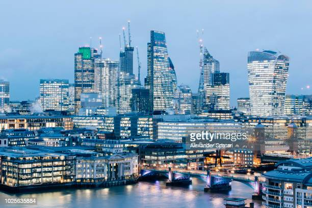 City of London financial district skyline elevated view at night with illuminated offie buildings