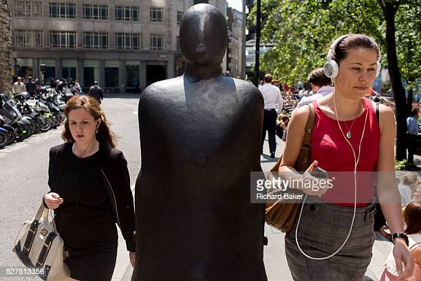 City of London office workers pass one of a pair of leaning figures by Anthony Gormley entitled Parralel Field part of Sculpture in the City a summer...