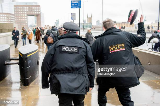 City of London Police officer has his hat blown off his head by the wind while pursuing protestors from the Green AntiCapitalist Front off the London...