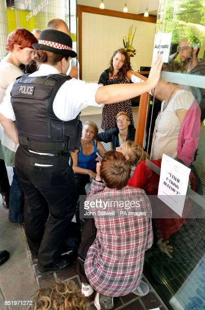 A City of London Police officer talks to a group of antifracking demonstrators as they sit with their hands superglued to each other at the offices...