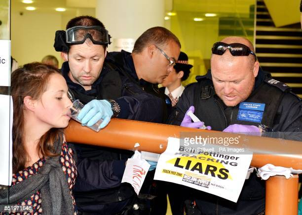A City of London Police officer uses a liquid to unglue a group of anti fracking demonstrators as they stand with their hands superglued to each...