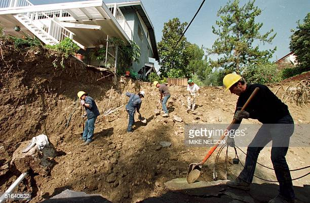 City of Los Angeles General Services workers labor to shore up mudslide damage to homes in the Canoga Park neighborhood of Los Angeles where some...