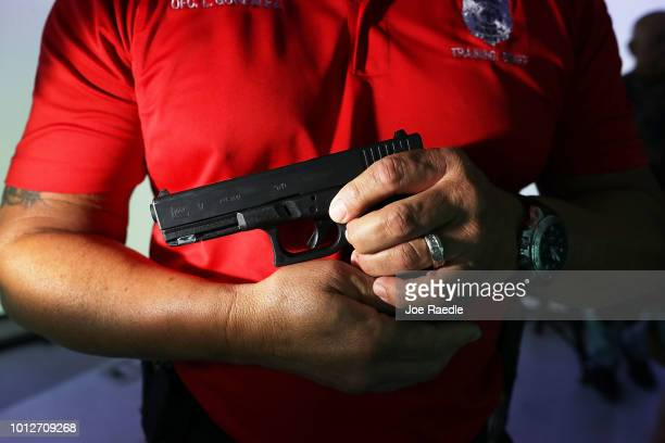 City of Miami police training officer Luis Gonzalez holds his pistol as he takes part in a demonstration of the Meggitt Training System FATS¨ 300LE...