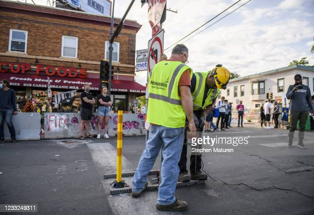 City of Minneapolis workers install a stop sign at the intersection of 38th street and Chicago Avenue at George Floyd Square on June 3, 2021 in...