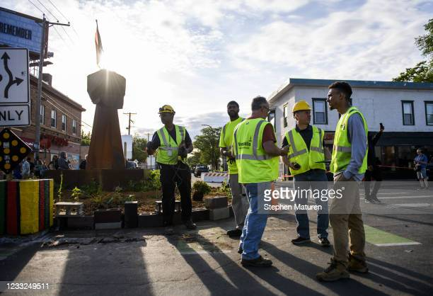 City of Minneapolis workers wrap up after installing stop signs at the intersection of 38th street and Chicago avenue at George Floyd Square on June...