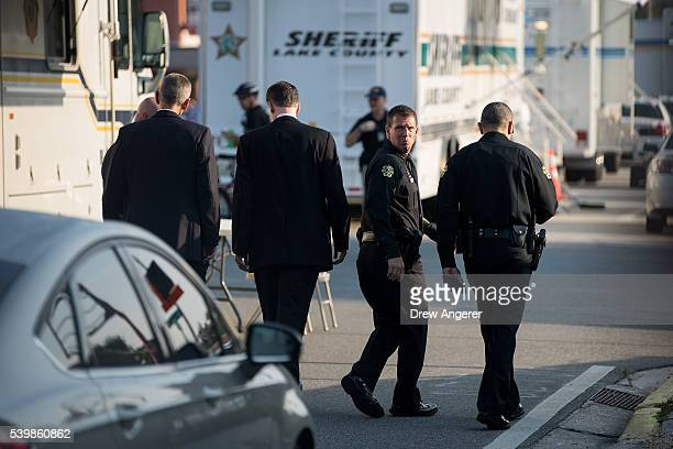 City of Orlando Police Chief John Mina walks with law enforcement officials back toward the crime scene after a press conference on South Orange...