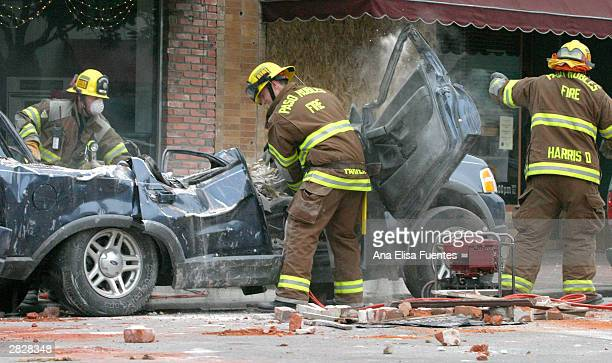City of Paso Robles firefighters Gary Sabin and Dave Parker pry open the door of a vehicle as firefighter Doug Harris shields himself from the...