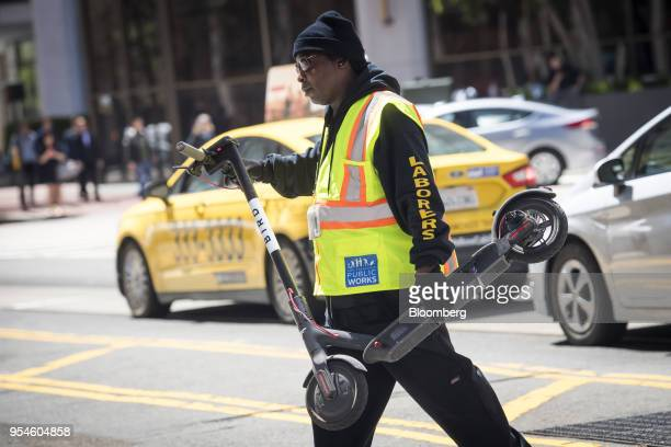 A City of San Francisco Public Works employee carries a a Bird Rides Inc shared electric scooter in San Francisco California US on Wednesday May 2...