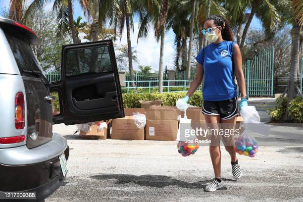 City of Sunrise employee places Easter eggs provided by the food bank Feeding South Florida into the vehicles of the needy on April 06, 2020 in...